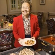 Seniorin füllt sich einen Teller auf