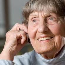 Pflegebedürftige Senioren lächelt und denkt nach