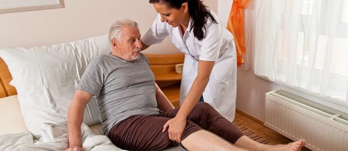 Senior wird von Pflegerin in Bett gebracht